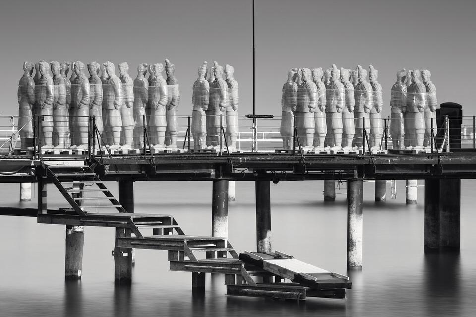 Langzeitbelichtung einer Terrakotta-Armee auf einem Steg.