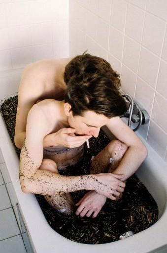Zwei Männer sitzen in einer schwarzen Badewanne und umarmen sich.