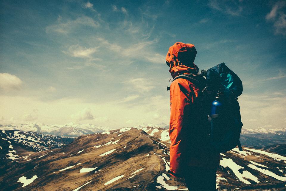 Eine Person mit Rucksack steht vor Gebirgsketten.