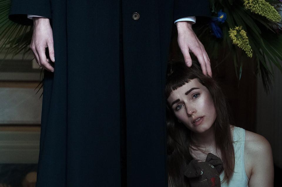 Mann legt seine Hand auf den Kopf einer jungen Frau unter ihm.
