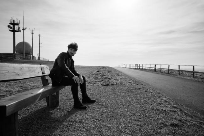 Mann auf Sitzbank vor einer Radarstation