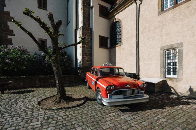 Rotes Taxi auf Klosterhof neben Baum