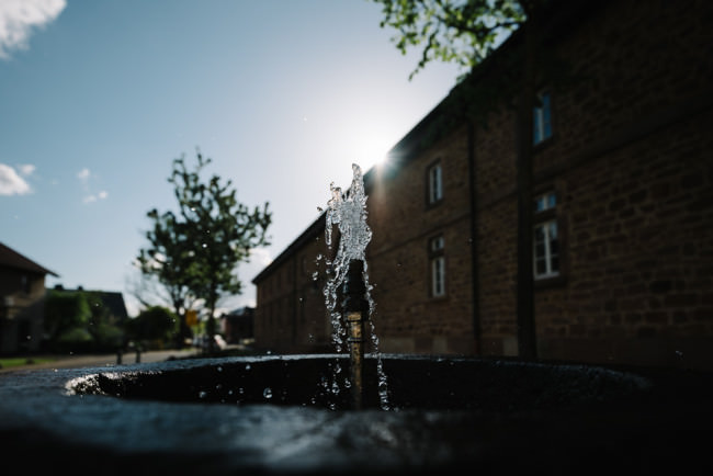 Aufsprudelnden Wasser eines Brunnens im Gegenlicht
