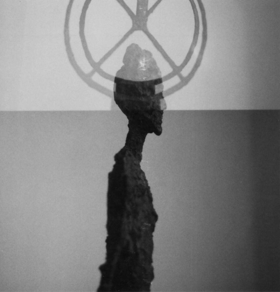 Eine figürliche Skulptur ist doppeltbelichtet mit einem Rad.