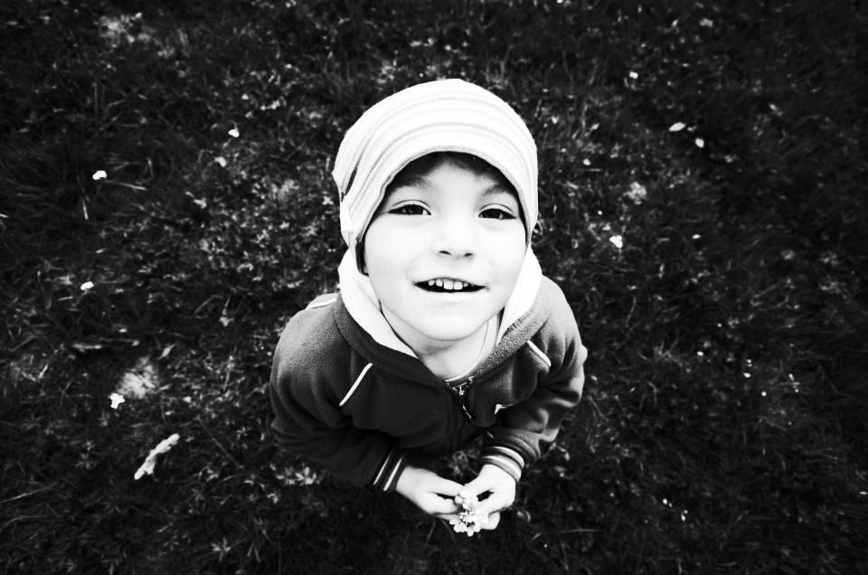Ein Junge, von oben auf einer Wiese stehend, gesehen, in schwarzweiß.