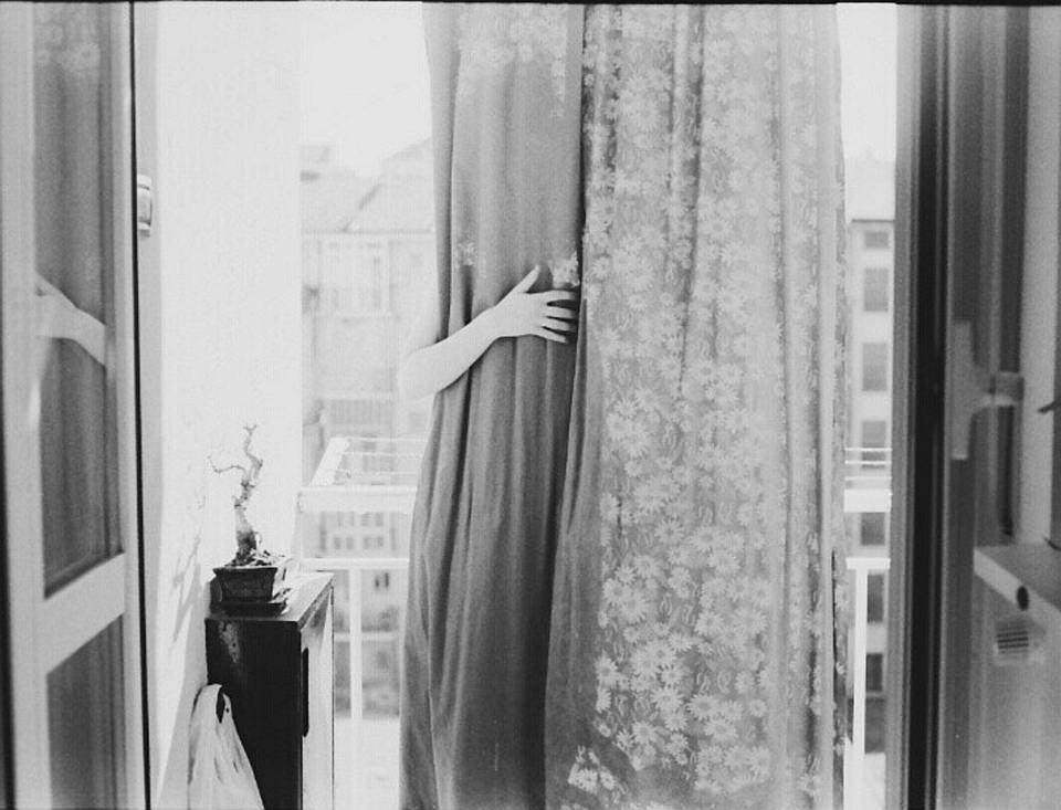 Hand greift hinter einem Blumenvorhang vor einem Fenster hervor.
