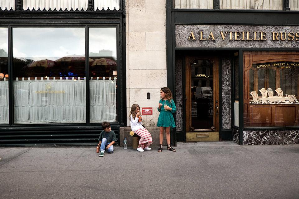 Kinder in einer Stadt vor einem Schaufenster.