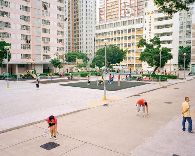 Menschen auf einem Sport- und Spielplatz zwischen Wohnhochhäusern.