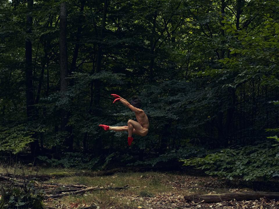 Ein Mann mit roter Farbe an Händen und Füßen springt im Wald.