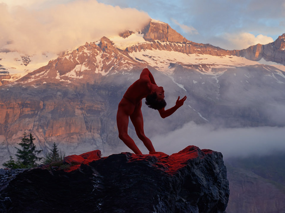 Ein mann voller roter Farbe in dramatischer Pose.