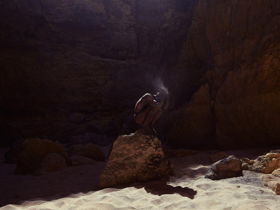 Ein Mann auf einem Stein am Strand