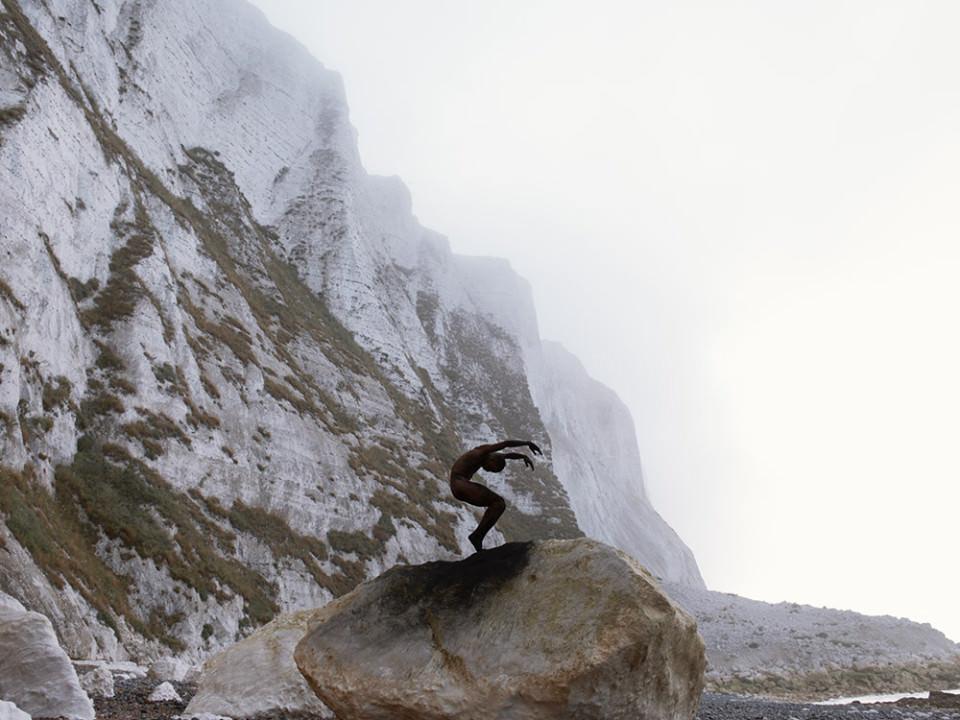 Ein Mann in Schwarz mit dramatischer Poase auf einem Felsen.