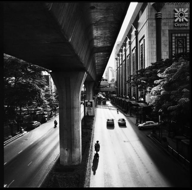 Autos und Rollerfahrer im Gegenlicht unter einer Brücke.