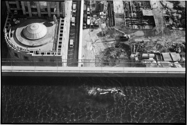 Eine Frau schwimmt in einem Becken, das auf einem Wolkenkratzer ist.
