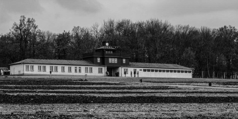 Langes Gebäude vor einem kahlen Wald und tristem Himmel, im Vordergrund ein leeres Feld.