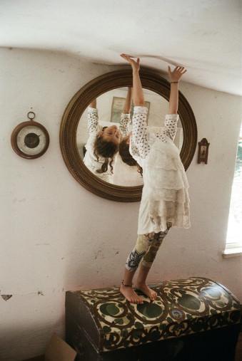 Ein Mädchen berührt die Decke und schaut dabei in den Spiegel