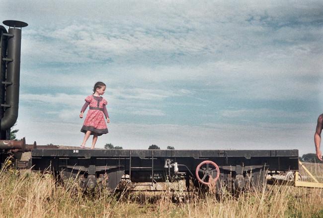Ein Kind steht auf einem alten Lastenzug. Sommer.