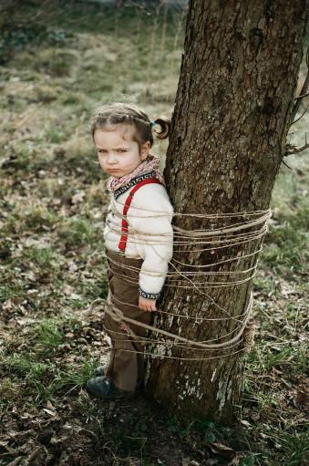 Ein Mädchen steht an einen Baum angebunden mit grimmiger Grimasse.