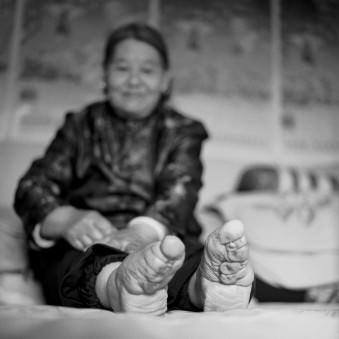 Eine Frau mit nackten kleinen Füßen auf einem Bett sitzend.