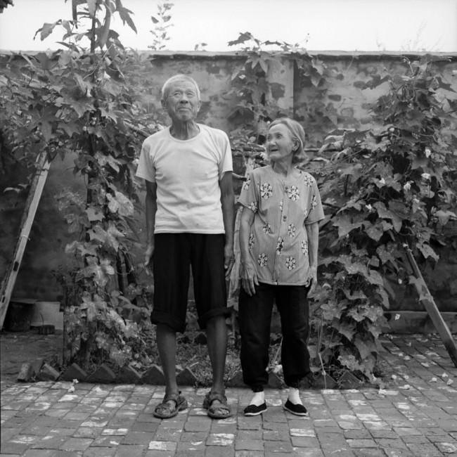 © Ein Mann und eine Frau lachend vor einer Mauer