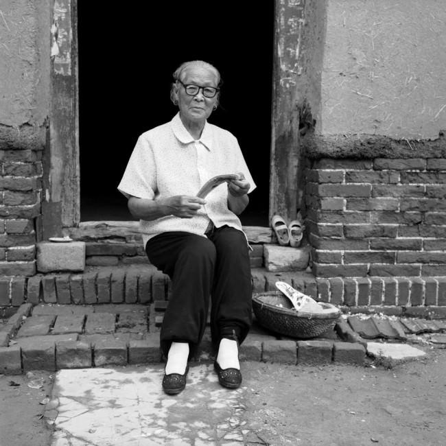 Eine Frau sitzt auf der Vortreppe zu ihrem Haus.