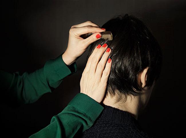 Eine Person kämmt einer Anderen das Haar.