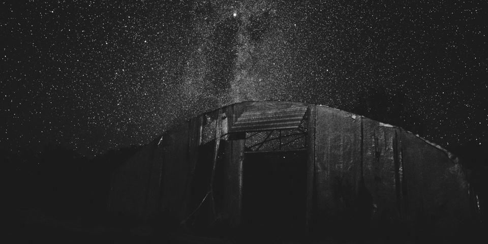 Ein älteres Gebäude vor Sternenhimmel.