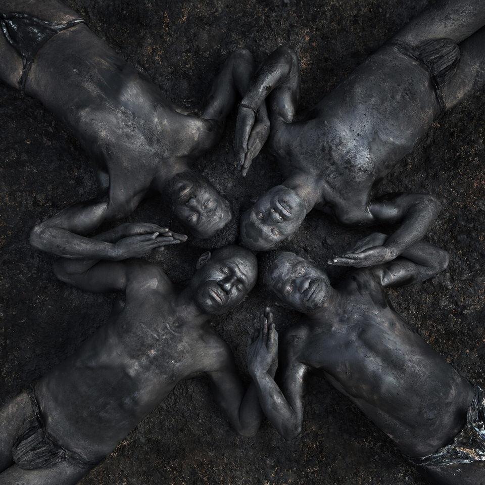 Männer mit Asche bemalt bilden ein Muster auf dem Boden.