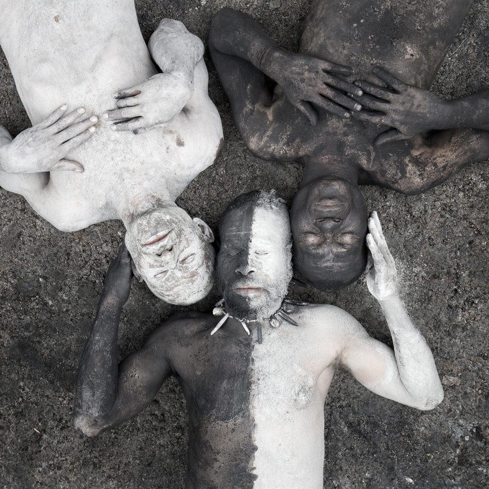 Drei Männer in schwarz und weiß bemalt liegen zusammen.