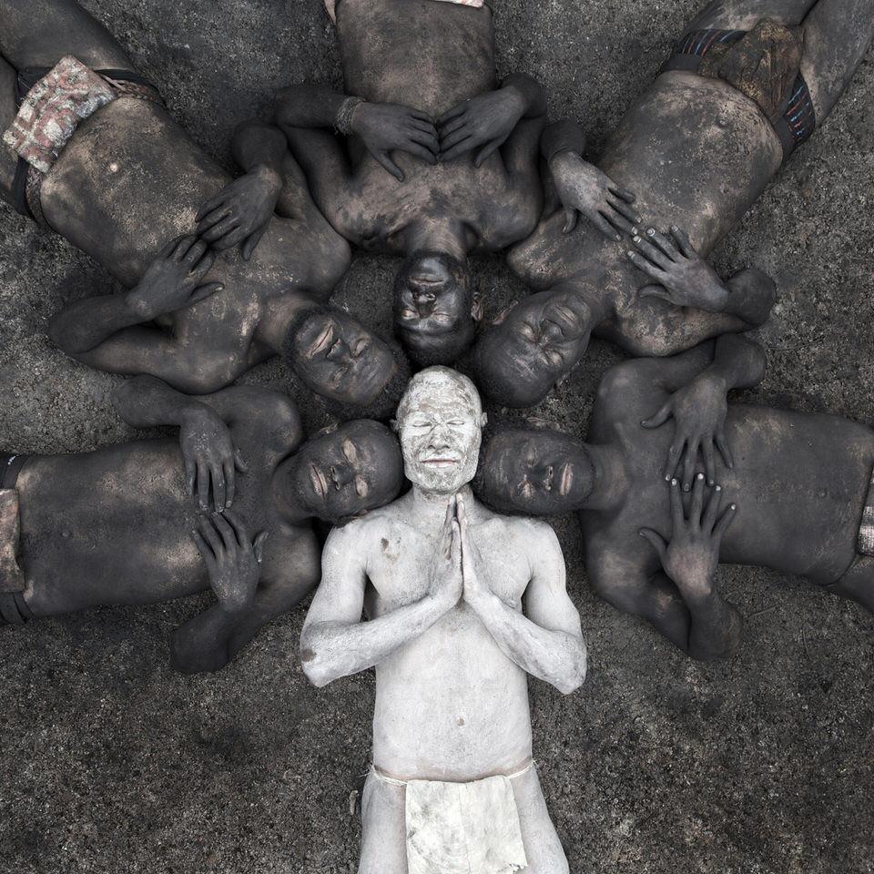 Ein weiß bemalter Mann umrandet von anderen schwarz bemalten Männern.