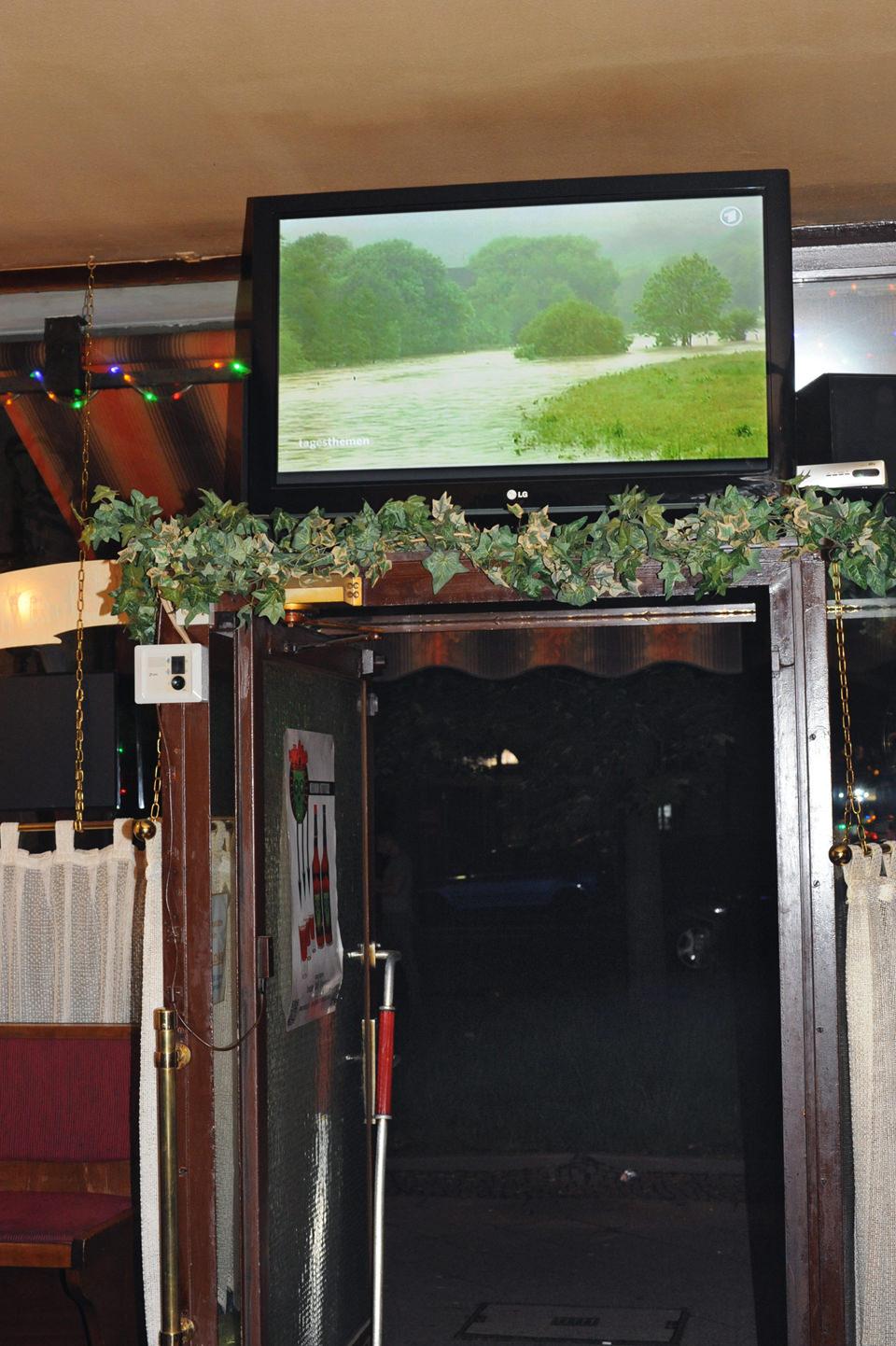 Ein Fernseher zeigt eine Landschaft in einer Bar.