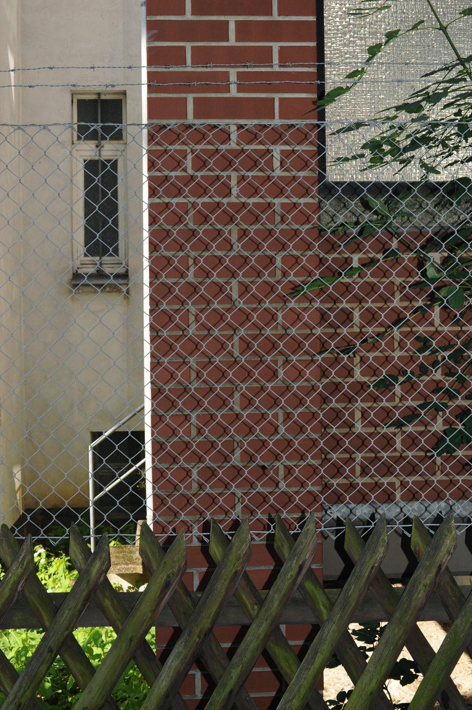 Ein Zaun verbirgt eine Wand.