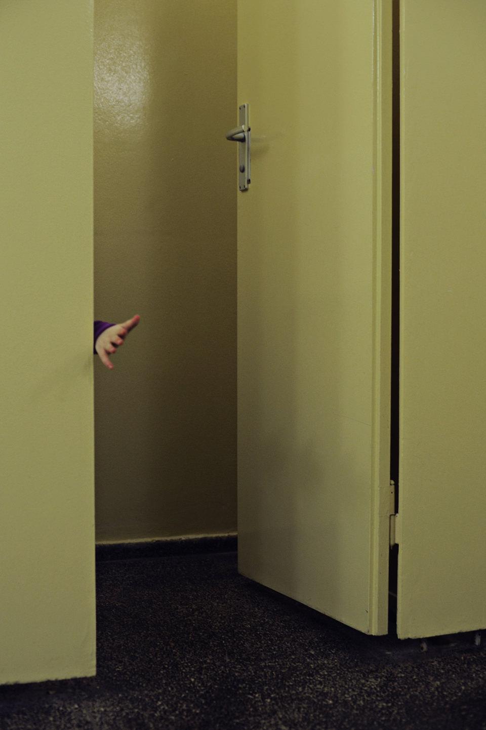 Eine Kinderhand greift durch eine Tür.