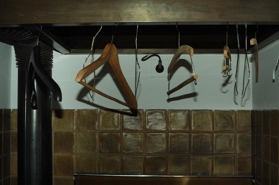 Kleiderbügel hängen an einem Balken.