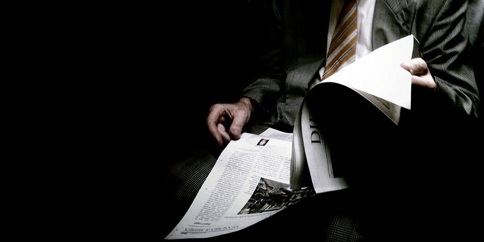 In der Dunkelheit Zeitung lesender Mann mit Anzug und Krawatte.