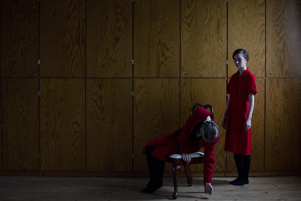 Zwei Frauen in Rot sitzen und stehe vor einer Holzvertäfelung.
