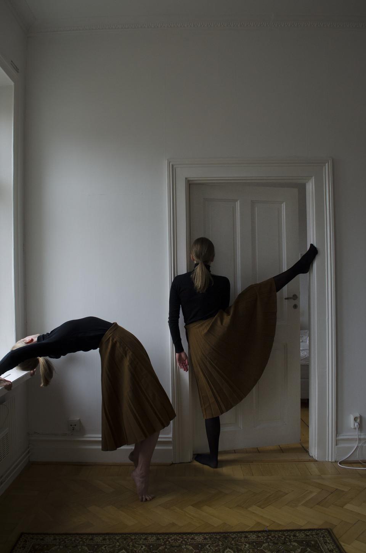 Zwei Frauen in braunen Röcken machen Verrenkungen in einem Zimmer.