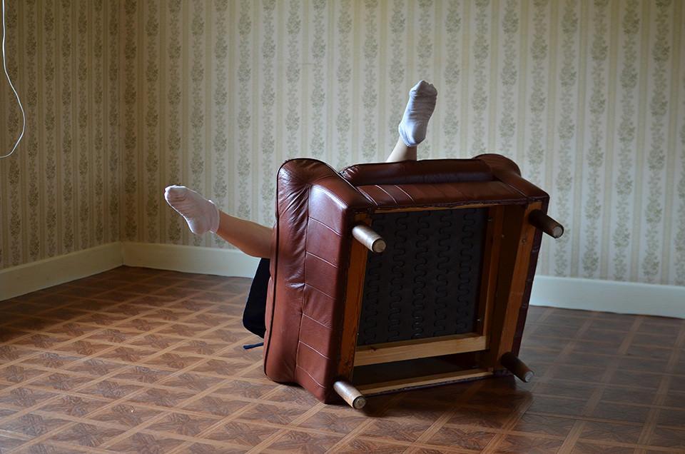 Beine mit Strümpfen schaune hinter einem ungekippten Sessel hervor.