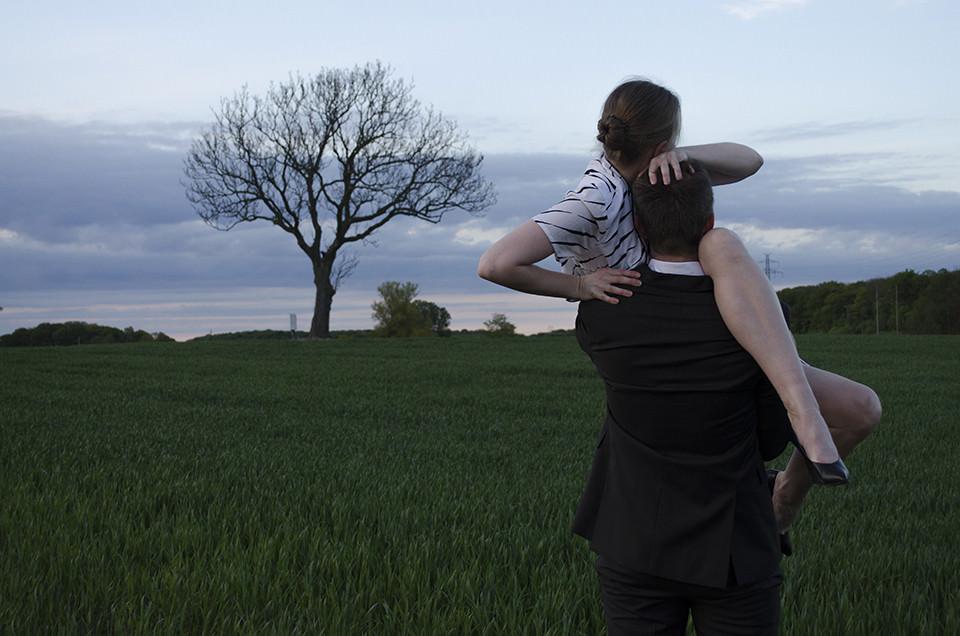 Ein Mann hält eine Frau auf einer Wiese auf dem Arm.