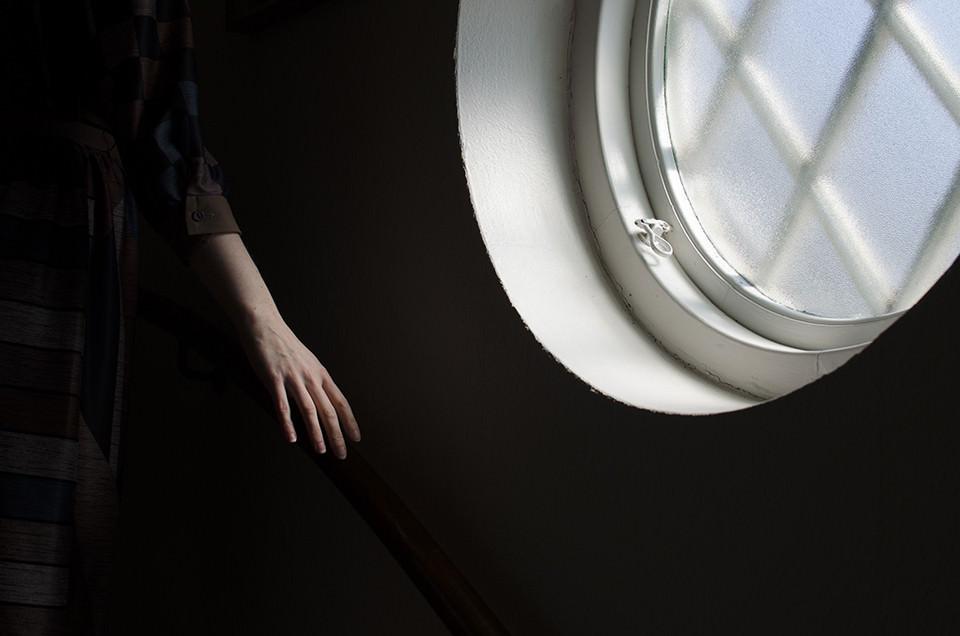 Frauenhand streift neben einem runden Fenster.