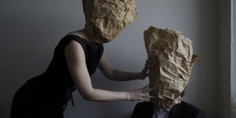 Zwei Personen mit Papiertüten auf dem Kopf beugen sich zueinander..
