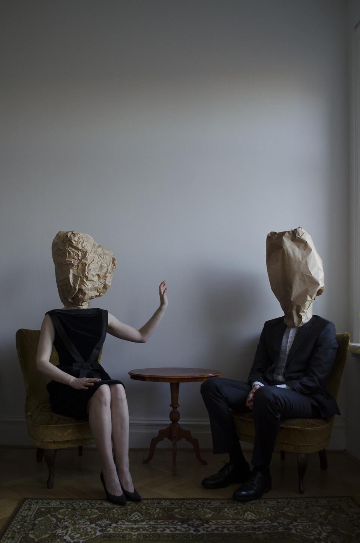 Zwei Personen mit Papiertüten auf dem Kopf sitzen am Tisch.