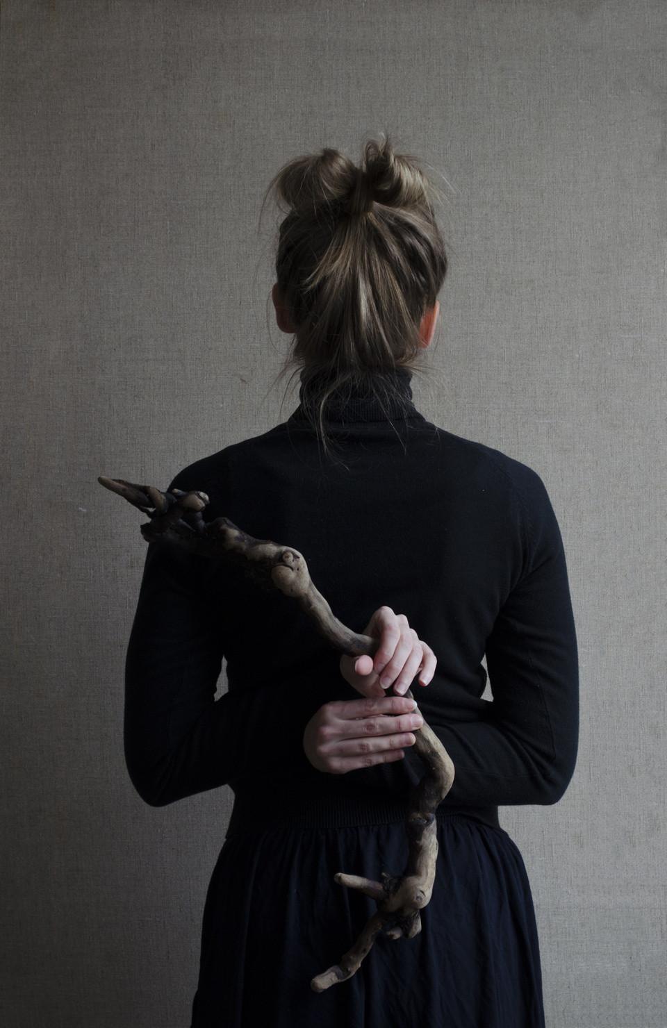 Frau hält einen knochigen Ast hinter ihrem Rücken.