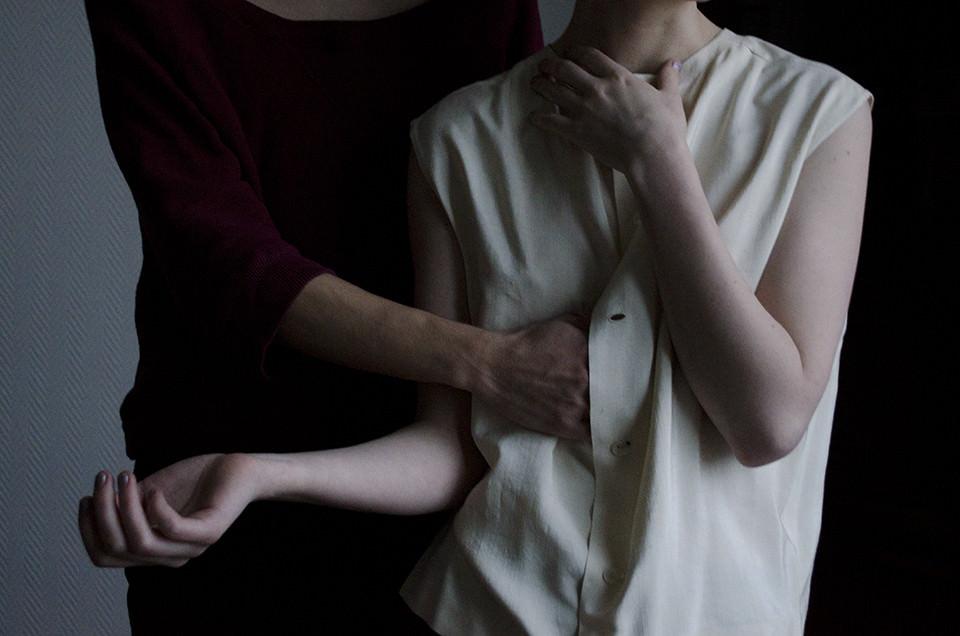 Eine Hand greift einer Frau in die Bluse.