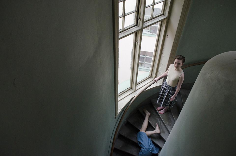 Zwei Frauen stehen und liegen auf einer Treppe.