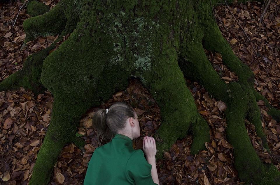 Eine grüngekleidete Frau liegt unter einem moosigen Baum.
