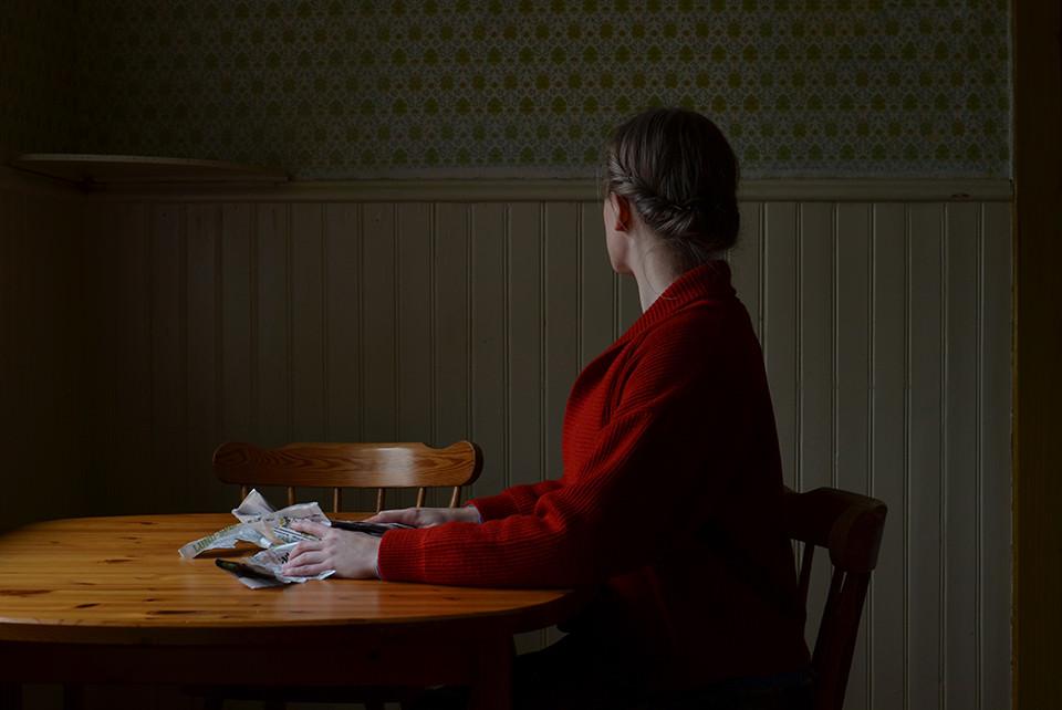 Eine Frau mit roter Jacke sitzt am Tisch und zerknällt Papier.