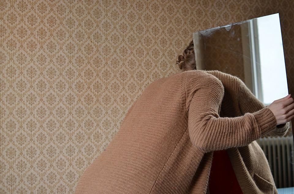 Eine Frau in rosa Strickjacke steckt ihren Kopf hinter einen Spiegel.