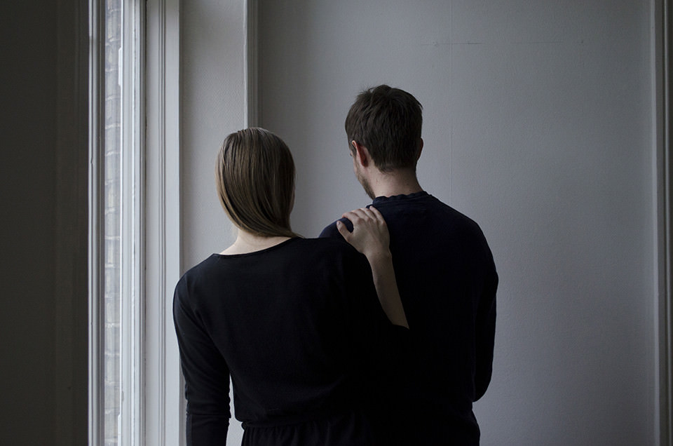 Zwei schwarz gekleidete Personen stehen mit dem Rücken zur Kamera.