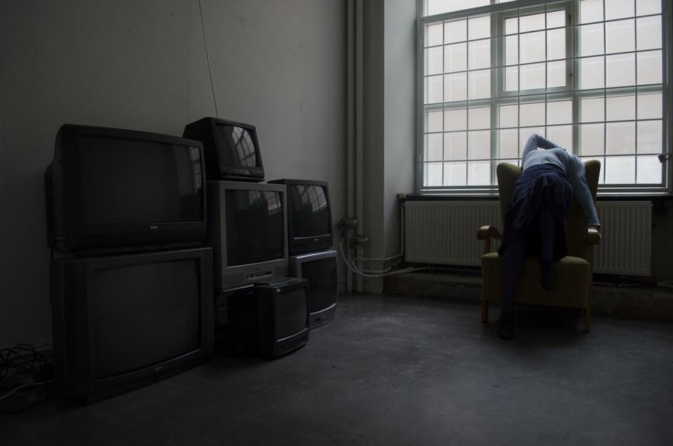 Vielen Fernseher sind aufgetürmt, daneben streckt sich eine Frau auf einem Sessel.